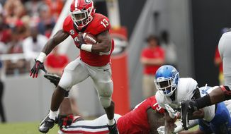 Georgia running back Elijah Holyfield (13) breaks through the Middle Tennessee defense for a big gain in the first half of an NCAA college football game Saturday, Sept. 15, 2018, in Athens, Ga. (AP Photo/John Bazemore)