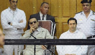 FILE - In this Sept. 14, 2013 file photo, former Egyptian President Hosni Mubarak, seated center left, and his two sons, Gamal Mubarak, left, and Alaa Mubarak attend a hearing in a courtroom in Cairo, Egypt.  Egyptian officials say police have detained the sons of former president Hosni Mubarak in connection with inside trading charges. They said the arrests were ordered Saturday, Sept. 15, 2018 by judge Ahmed Aboul-Fetouh before he adjourned the hearings to October 20. (AP Photo/Mohammed al-Law, File)
