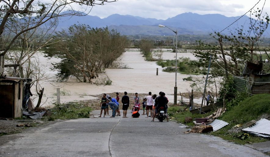 Residents stand by a flooded road following the onslaught of Typhoon Mangkhut in Tuguegarao city in Cagayan province, northeastern Philippines, Saturday, Sept. 15, 2018. The typhoon slammed into the Philippines northeastern coast early Saturday, it's ferocious winds and blinding rain ripping off tin roof sheets and knocking out power, and plowed through the agricultural region at the start of the onslaught. (AP Photo/Aaron Favila)