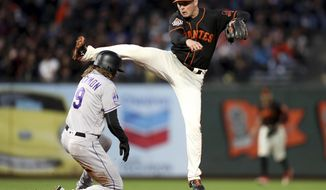 San Francisco Giants second baseman Joe Panik (12) forces out Colorado Rockies center fielder Charlie Blackmon (19) and completes a double play in the fourth inning of a baseball game in San Francisco, Saturday, Sept. 15, 2018. (AP Photo/Scot Tucker)