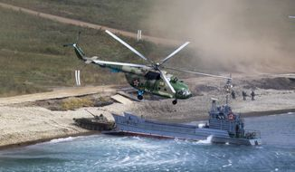 "A Russian navy landing vessel unloads an armored vehicle as a military helicopter flies overhead during Russian military maneuvers Vostok 2018 on the training ground ""Klerk"", about 50 kilometers (31 miles) south of Vladivostok, Russian Far East port, Russia, Saturday, Sept. 15, 2018. The weeklong Vostok 2018 maneuvers are the largest war games Russia ever had. (AP Photo/Sergei Grits)"