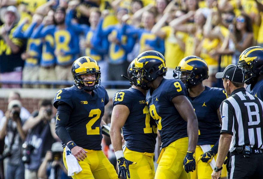 Michigan quarterback Shea Patterson (2) and wide receiver Donovan Peoples-Jones (9) celebrate with teammates their touchdown in the second quarter of an NCAA college football game against SMU in Ann Arbor, Mich., Saturday, Sept. 15, 2018. (AP Photo/Tony Ding)