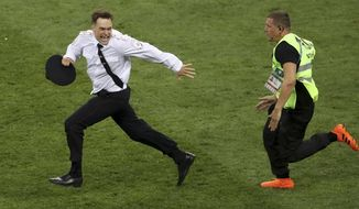 FILE - In this Sunday, July 15, 2018 file photo, Pyotr Verzilov invading the pitch, runs away as a steward tries to stop him during the France and Croatia 2018 World Cup final match in the Luzhniki Stadium in Moscow, Russia. Of the four people who protested on the field during the World Cup soccer final in Moscow, one is now in intensive care and another spent part of the week in a jail cell.   On Wednesday, Sept. 12, 2018 five days after speaking to the AP, Verzilov was admitted to the intensive care ward of a Moscow hospital. (AP Photo/Thanassis Stavrakis, File)