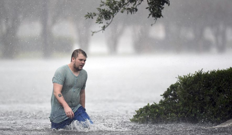 Jake Head walks through heavy rain from tropical storm Florence in Wilmington, N.C., Saturday, Sept. 15, 2018.  (Matt Born/The Star-News via AP)