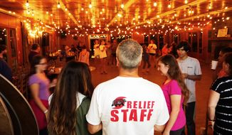 Camp Cedar Cliff directors Tim and Libby Brady watched families and friends swing dancing in the dining hall this weekend. The activity was designed to cheer up evacuees from the dangers of Florence. (Julia Airey/The Washington Times)
