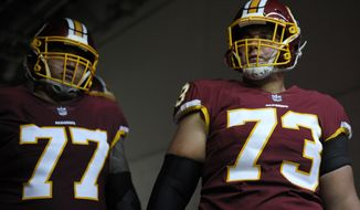 Washington Redskins offensive guard Shawn Lauvao (77) and center Chase Roullier (73) stand in the tunnel prior to an NFL football game against the Indianapolis Colts, Sunday, Sept. 16, 2018, in Landover, Md. (AP Photo/Mark Tenally)