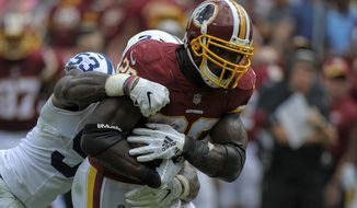 Washington Redskins running back Adrian Peterson (26) is tackled by Indianapolis Colts linebacker Darius Leonard (53) during an NFL football game between the Indianapolis Colts and Washington Redskins, Sunday, Sept. 16, 2018, in Landover, Md. (AP Photo/Mark Tenally)