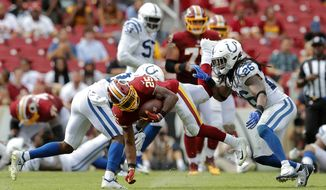 Washington Redskins running back Chris Thompson, center, is tackled by Indianapolis Colts cornerback Kenny Moore, left, and defensive back Clayton Geathers in the second half of an NFL football game, Sunday, Sept. 16, 2018, in Landover, Md. (AP Photo/Carolyn Kaster)