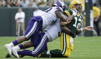 Green Bay Packers' Aaron Rodgers is hit after throwing during the second half of an NFL football game against the Minnesota Vikings Sunday, Sept. 16, 2018, in Green Bay, Wis. (AP Photo/Mike Roemer)
