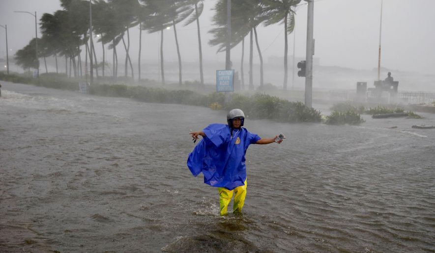 FILE - In this Saturday, Sept. 15, 2018, file photo, a man directs traffic to avoid a flooded street at the onslaught of Typhoon Mangkhut which barreled into the northeastern Philippines before dawn in Manila, Philippines. (AP Photo/Bullit Marquez, File)