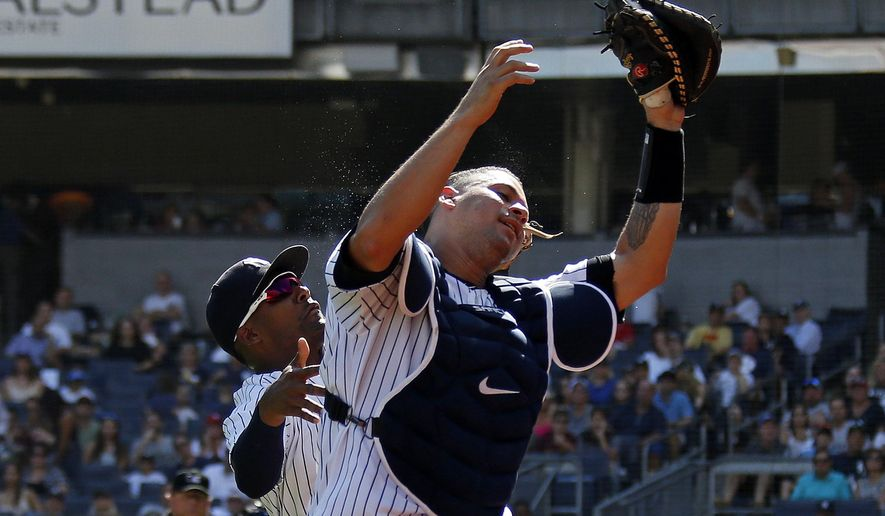 New York Yankees catcher Gary Sanchez makes an out on Toronto Blue Jays' Yangervis Solarte (not pictured) as he collides with Yankees third baseman Miguel Andujar during the fourth inning of a baseball game on Sunday, Sept. 16, 2018, in New York. (AP Photo/Adam Hunger)