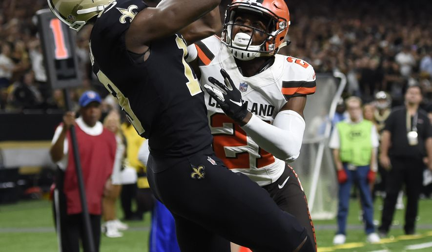 New Orleans Saints wide receiver Michael Thomas, left, scores a touchdown over Cleveland Browns cornerback Denzel Ward during the second half of an NFL football game in New Orleans, Sunday, Sept. 16, 2018. (AP Photo/Bill Feig)