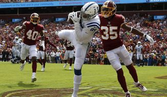 Indianapolis Colts tight end Eric Ebron, center, catches a pass for a touchdown in front of Washington Redskins defensive back Montae Nicholson (35) and linebacker Josh Harvey-Clemons (40) in the first half of an NFL football game, Sunday, Sept. 16, 2018, in Landover, Md. (AP Photo/Alex Brandon)