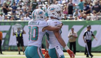 Miami Dolphins' A.J. Derby (85) celebrates with Danny Amendola (80) after scoring a touchdown during the first half of an NFL football game against the New York Jets Sunday, Sept. 16, 2018, in East Rutherford, N.J. (AP Photo/Bill Kostroun)