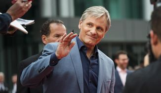 """Actor Viggo Mortensen waves to fans as he arrives ahead of the screening of """"Green Book"""" during the Toronto International Film Festival in Toronto, on Tuesday, Sept. 11, 2018. (Christopher Katsarov/The Canadian Press via AP)"""