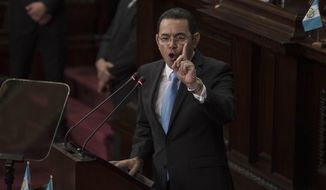 Guatemalan President Jimmy Morales delivers his speech during a a session to celebrate the country's independence, in Guatemala City, Wednesday, Sept. 12, 2018. Thousands of police and at least 50 heavily-armed soldiers set a security cordon around congress that greatly exceeded normal, while about 8,000 protesters called for Morales' resignation and expressed their opposition to his decision not to renew the mandate of a United Nation's-backed anti-corruption commission. (AP Photo/Oliver de Ros)