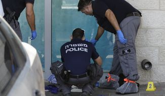 Israeli police investigates at the scene of an stabbing attack in the West Bank settlement of Gush Etzion Sunday, Sept. 15, 2018. The Israeli military says a Palestinian attacker has stabbed and critically wounded an Israeli man in front of a mall. (AP Photo/Mahmoud Illean)