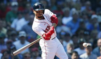 Boston Red Sox's Mookie Betts hits a sacrifice fly that scored Rafael Devers during the third inning of a baseball game against the New York Mets in Boston, Sunday, Sept. 16, 2018. (AP Photo/Michael Dwyer)