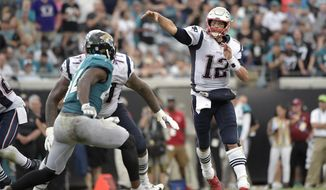 New England Patriots quarterback Tom Brady (12) throws a 29-yard pass to wide receiver Chris Hogan over Jacksonville Jaguars linebacker Myles Jack, left, during the second half of an NFL football game, Sunday, Sept. 16, 2018, in Jacksonville, Fla. (AP Photo/Phelan M. Ebenhack)