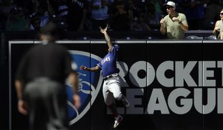Texas Rangers left fielder Willie Calhoun can't reach a home run hit by the San Diego Padres' Hunter Renfroe during the first inning of a baseball game Sunday, Sept. 16, 2018, in San Diego. (AP Photo/Gregory Bull)