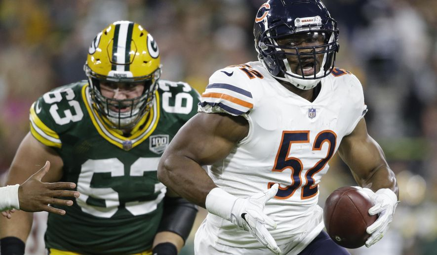 FILE - In this Sunday, Sept. 9, 2018, file photo, Chicago Bears' Khalil Mack intercepts a pass and returns it for a touchdown during the first half of an NFL football game against the Green Bay Packers in Green Bay, Wis. Mack sat out offseason workouts and the preseason, had just one week to learn a new system following a blockbuster trade and still managed to dominate in his debut for the Chicago Bears. The Bears hope for more of that when they host Russell Wilson and the Seattle Seahawks on Monday night, Sept. 17. (AP Photo/Jeffrey Phelps, File)