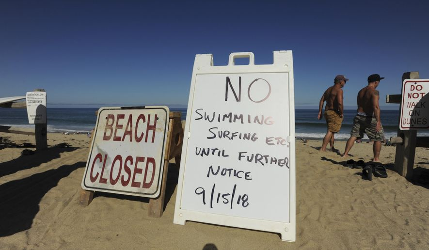 Two signs at the top of the dune at Newcomb Hollow Beach alert visitors that the beach is closed to swimming, Saturday, Sept. 15, 2018, in Wellfleet, Mass. A Revere man died after being bitten by a shark off Newcomb Hollow Beach on Saturday. (Merrily Cassidy/The Cape Cod Times via AP)