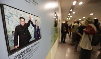 A photo, from the April 27, 2018, inter-Korean summit between South Korean President Moon Jae-in and North Korean leader Kim Jong-un, left, is displayed at the Unification Observation Post in Paju, near the border with North Korea, South Korea, Sunday, Sept. 16, 2018. Moon is to fly to Pyongyang, North Korea, next Tuesday, Sept. 18, for a three-day trip that he says will focus on facilitating talks between the United States and North Korea and finding ways to ease a military standoff along the Koreas' heavily fortified border. (AP Photo/Ahn Young-joon)