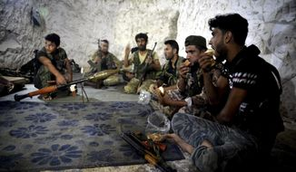 FILE - In this Sunday, Sept. 9, 2018 file photo, fighters with the Free Syrian army eat in a cave where they live, in the outskirts of the northern town of Jisr al-Shughur, Syria, west of the city of Idlib. As the decisive battle for Idlib looms, a motley crew of tens of thousands of Syrian opposition fighters, including some of the world's most radical, are digging their heels_ looking for ways to salvage what is possible of an armed rebellion that at one point in the seven-year conflict controlled more than half of the country. (Ugur Can/DHA via AP, File)