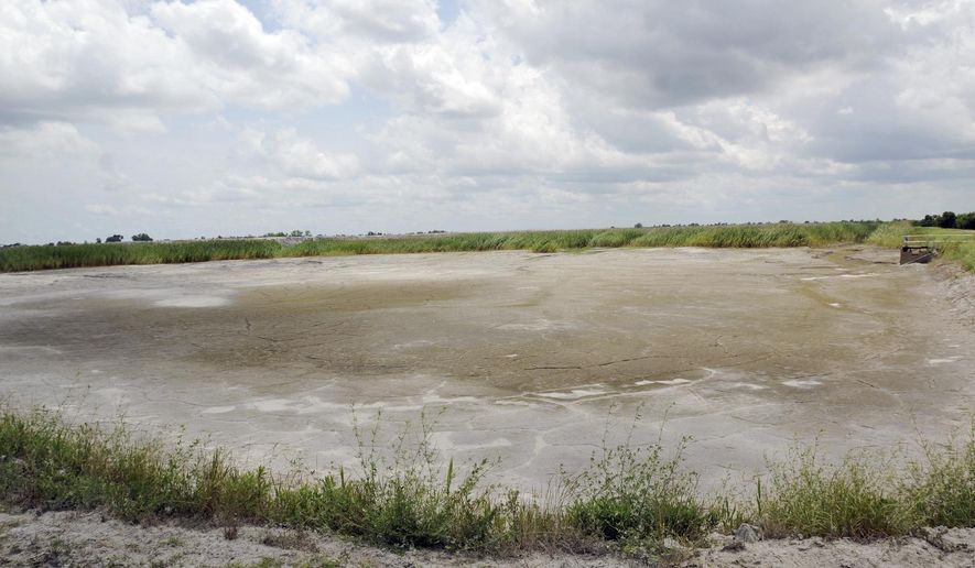 FILE - In this June 23, 2014 file photo, the dried-up bed of an inactive coal ash pond is seen at Duke Energy's Sutton plant in Wilmington, N.C. Duke Energy says heavy rains from Florence have caused a slope to collapse at a coal ash landfill at a closed power station near the North Carolina coast. Duke spokeswoman Paige Sheehan said Saturday night, Sept. 15, 2018, that about 2,000 cubic yards of ash have been displaced at the L. V. Sutton Power Station outside Wilmington. (Mike Spencer/The Star-News via AP)