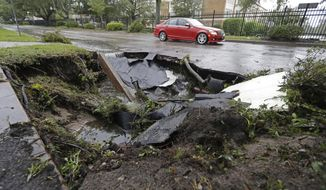A car travels past a sinkhole in downtown Wilmington, N.C., after Hurricane Florence traveled through the area Sunday, Sept. 16, 2018. (AP Photo/Chuck Burton)