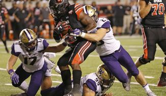 Utah running back Zack Moss (2) is tackled by Washington's Ben Burr-Kirven (25), Greg Gaines (99) and Tevis Bartlett (17) in the first half during an NCAA college football game, Saturday, Sept. 15, 2018, in Salt Lake City. (AP Photo/Rick Bowmer)