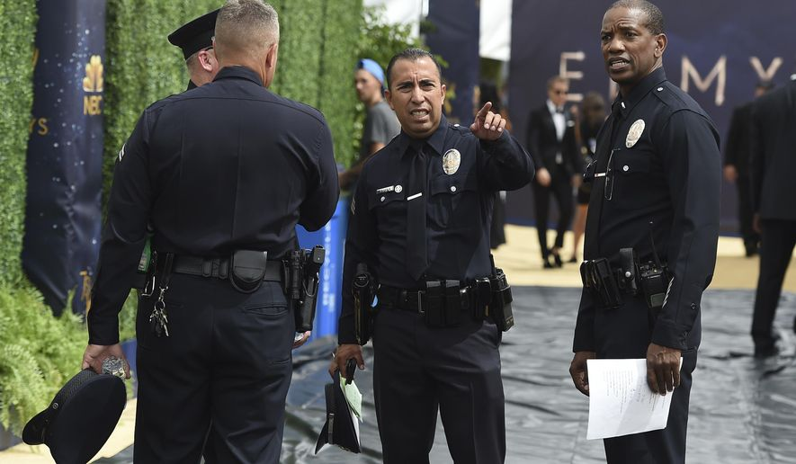 Police officers meet on the carpet before the start of the 70th Primetime Emmy Awards on Monday, Sept. 17, 2018, at the Microsoft Theater in Los Angeles. (Photo by Jordan Strauss/Invision/AP)