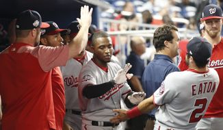Washington Nationals' Victor Robles, center, is congratulated by teammates after hitting a home run during the third inning of a baseball game against the Miami Marlins, Monday, Sept. 17, 2018, in Miami. (AP Photo/Wilfredo Lee)