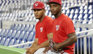 Washington Nationals' Victor Robles, right, and Pedro Severino wait for the start of batting practice before the start of a baseball game against the Miami Marlins, Monday, Sept. 17, 2018, in Miami. (AP Photo/Wilfredo Lee)