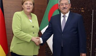 German Chancellor Angela Merkel shakes hands with Algerian Prime Minister Ahmed Ouyahia ahead of talks in Algiers, Monday Sept.17, 2018. Merkel is visiting Algeria for a day to promote bilateral ties and discuss migration and the situation in neighboring Libya. (AP Photo/Anis Belghoul)