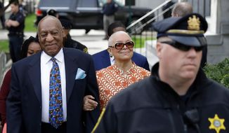 FILE - In this April 24, 2018, file photo, Bill Cosby, left, arrives with his wife, Camille, for his sexual assault trial, at the Montgomery County Courthouse in Norristown, Pa. Cosby's wife wants a Pennsylvania ethics board to investigate the judge set to sentence her husband Sept. 24, on felony sex assault charges. (AP Photo/Matt Slocum, File)