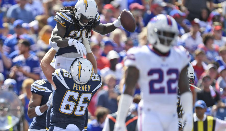Los Angeles Chargers' Melvin Gordon, top left, celebrates a touchdown with Dan Feeney during the first half of an NFL football game against the Buffalo Bills, Sunday, Sept. 16, 2018, in Orchard Park, N.Y. (AP Photo/Adrian Kraus)