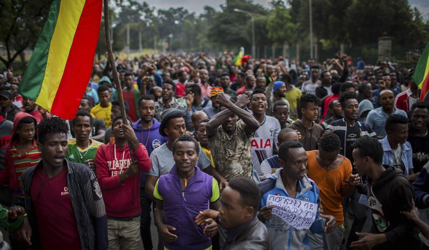 """Thousands of protestors from the capital and those displaced by ethnic-based violence over the weekend in Burayu, demonstrate to demand justice from the government in Addis Ababa, Ethiopia Monday, Sept. 17, 2018. Several thousand Ethiopians have gone out onto the streets of the capital to protest ethnic-based attacks in the outskirts of the city in which more than 20 people died over the weekend. Banner in Amharic reads """"The government should stop the attacks against our people."""" (AP Photo/Mulugeta Ayene)"""