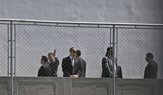 Guatemalan President Jimmy Morales, second from left, waves to photographers as he is surrounded by security guards before the inaugurating a soccer field in Mixco, Guatemala, Monday, Sept. 17, 2018. Morales' government will defy a ruling by the country's top court and block the return of Ivan Velasquez, who is leading a U.N.-backed anti-corruption commission. (AP Photo/Moises Castillo)