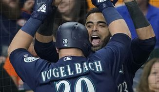 Seattle Mariners' Daniel Vogelbach (20) celebrates with Nelson Cruz (23) after hitting a grand slam against the Houston Astros during the eighth inning of a baseball game Monday, Sept. 17, 2018, in Houston. (AP Photo/David J. Phillip)