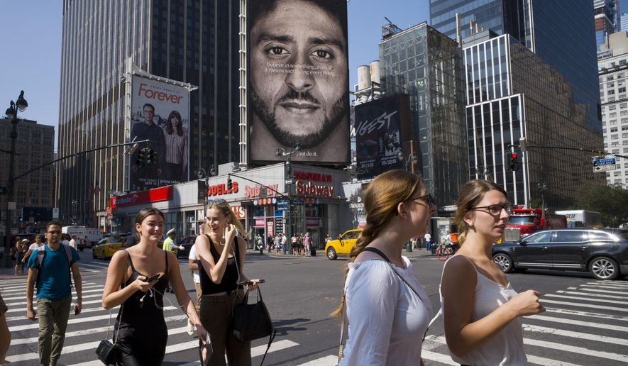 In this Sept. 6, 2018, photo, people in New York walk past a Nike advertisement featuring former San Francisco 49ers quarterback Colin Kaepernick, known for kneeling during the national anthem to protest police brutality and racial inequality. In response to Nike's support of Kaepernick, the Rhode Island town of North Smithfield is considering asking its departments to refrain from purchasing Nike products. (AP Photo/Mark Lennihan) **FILE**
