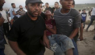 Protesters evacuate injured teen near the fence of Gaza Strip border with Israel during a protest on the beach near Beit Lahiya, northern Gaza Strip, Monday, Sept. 17, 2018. (AP Photo/Adel Hana)