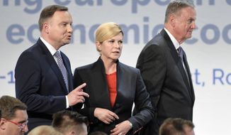 Croatian President Kolinda Grabar-Kitarovic, center, stands next to Polish President Andrzej Duda, left, as James Logan Jones, right, Interim Chairman of the Atlantic Council of the United States walks by, at the Three Seas Initiative Business Forum in Bucharest, Romania, Monday, Sept. 17, 2018. U.S. President Donald Trump has reaffirmed Washington's support for a business summit that aims to boost connectivity in Eastern Europe and improve ties between the region and the U.S.(AP Photo/Andreea Alexandru)