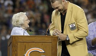 Former Chicago Bears and Hall of Fame linebacker Brian Urlacher receives a Ring of Excellence from Chicago Bears owner Virginia Halas McCaskey during the halftime of an NFL football game Monday, Sept. 17, 2018, in Chicago. (AP Photo/Nam Y. Huh)