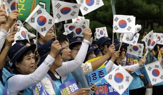 """South Koreans wave their national flags during a rally to wish for the successful inter-Korean summit near the presidential Blue House in Seoul, Tuesday, Sept. 18, 2018. South Korean President Moon Jae-in said Monday that he will push for """"irreversible, permanent peace,"""" and for better dialogue between Pyongyang and Washington, during """"heart-to-heart"""" talks with North Korean leader Kim Jong Un this week. The signs read: """" Denuclearization."""" (AP Photo/Ahn Young-joon)"""