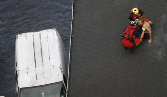 U.S. Coast Guard rescue swimmer Samuel Knoeppel, top, and Randy Haba, bottom left, talk to Willie Schubert of Pollocksville, N.C., as he is rescued from a rooftop in Pollocksville, Monday, Sept. 17, 2018. (AP Photo/Steve Helber)