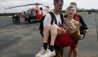 An unidentified family member carries Ruth Brady to safety at the Wilmington airport in Wilmington, N.C., Monday, Sept. 17, 2018. Brady was one of several family members rescued by a Coast Guard helicopter crew north of Wilmington. (AP Photo/Steve Helber)
