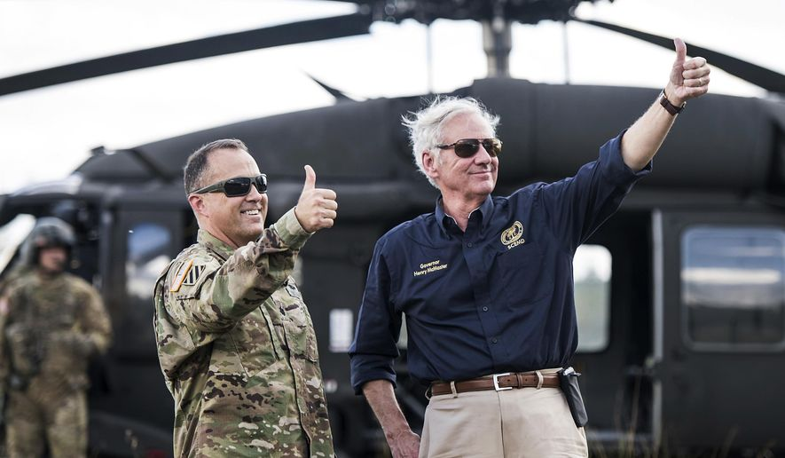 South Carolina Gov. Henry McMaster, right, and National Guard Lt. Col. Jay McElveen give thumbs-up to rescue workers after Hurricane Florence struck the Carolinas, Monday, Sept. 17, 2018, near Wallace, S.C. A fire rescue team saved two people stuck on the roof of a vehicle in floodwaters caused by the storm. (AP Photo/Sean Rayford)