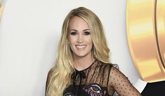 In this June 22, 2018, file photo, Carrie Underwood attends the 2018 Radio Disney Music Awards in Los Angeles. Underwood says she turned to God after experiencing three miscarriages in the past two years. (Photo by Richard Shotwell/Invision/AP, File)
