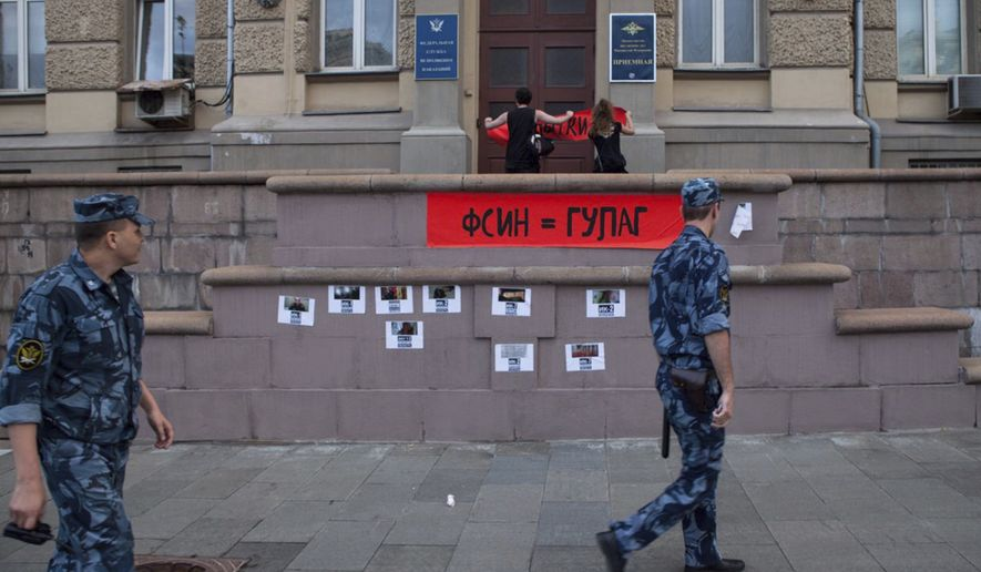 Activists of the feminist protest group Pussy Riot, fix a poster reading ' Federal Penitentiary service = GULAG', on the wall of the Federal Penitentiary building in Moscow, Russia, Tuesday, Aug. 7, 2018. Pussy Riot are protesting against alleged torture in Russian prisons. (AP Photo/ Alexander Sofeev)